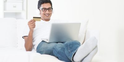 Asian man internet shopping indoor relaxed