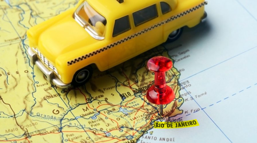 Close-up of a red pushpin on a map of Rio de Janeiro and a taxi car
